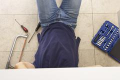 Plumber Working On Sink In Kitchen - stock photo