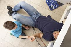 Son Helping Father To Mend Sink In Kitchen Stock Photos