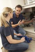 Plumber Teaching Apprentice To Fix Kitchen Sink In Home Stock Photos