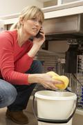 Woman Mopping Up Leaking Sink On Phone To Plumber - stock photo