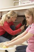 Daughter Helping Mother To Mop Up Leaking Sink - stock photo