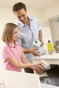 Stock Photo of Father And Daughter Recyling Waste At Home