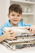 Young Boy Recyling Newspapers At Home Stock Photos
