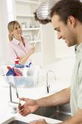 Couple Doing Housework In Kitchen Together - stock photo
