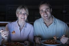 Couple Enjoying Meal Whilst Watching TV Stock Photos