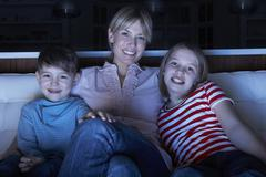 Mother And Children Watching Programme On TV Sitting On Sofa Together Stock Photos