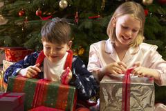 Children Opening Christmas Present In Front Of Tree - stock photo