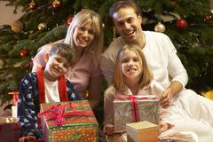 Family Opening Christmas Present In Front Of Tree Stock Photos