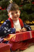 Young Boy Opening Christmas Present In Front Of Tree Stock Photos