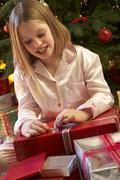 Young Girl Opening Christmas Present In Front Of Tree Stock Photos