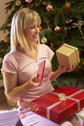 Woman Opening Christmas Present In Front Of Tree Stock Photos