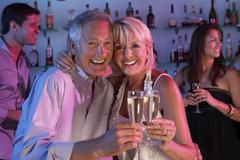 Senior Couple Having Fun In Busy Bar Stock Photos