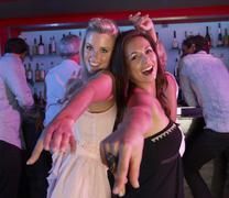 Two Young Women Having Fun In Busy Bar Stock Photos
