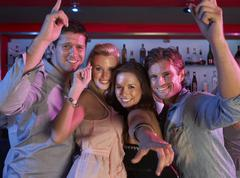 Stock Photo of Group Of Young People Having Fun In Busy Bar