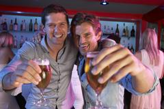 Two Young Men Having Fun In Busy Bar - stock photo