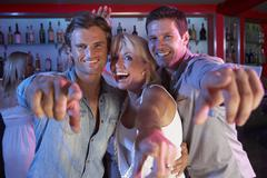 Senior Woman Having Fun In Busy Bar With Two Young Men - stock photo