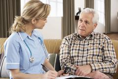 Senior Man Talking To Health Visitor At Home Stock Photos