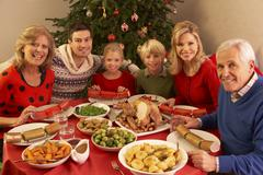 Three Generation Family Enjoying Christmas Meal At Home Stock Photos