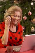 Senior Woman Shopping Online For Christmas Gifts On Phone Stock Photos