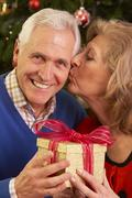 Senior Couple Exchanging Christmas Gifts Stock Photos