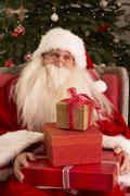 Santa Claus Sitting In Armchair In Front Of Christmas Tree Stock Photos