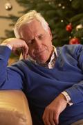 Tired Senior Man Relaxing In Front Of Christmas Tree - stock photo