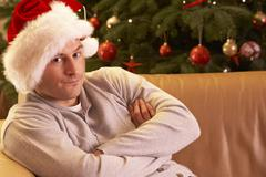 Man Relaxing In Front Of Christmas Tree Stock Photos