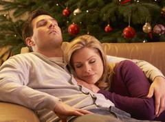 Tired Couple Relaxing In Front Of Christmas Tree Stock Photos