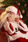 Santa Claus Making Rude Gesture To Camera In Front Of Christmas Tree Stock Photos