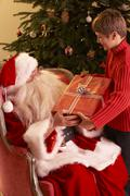 Santa Claus Giving Gift To Boy In Front Of Christmas Tree - stock photo