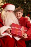 Santa Claus Giving Gift To Boy In Front Of Christmas Tree Stock Photos