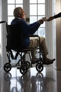 Disabled Senior Man Sitting In Wheelchair Being Handed Cup - stock photo