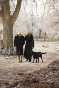 Senior Couple On Winter Walk With Dog Through Frosty Landscape - stock photo