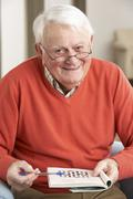 Senior Man Relaxing In Chair At Home Completing Crossword - stock photo