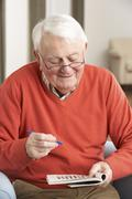 Senior Man Relaxing In Chair At Home Completing Crossword Stock Photos