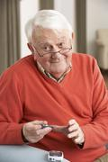 Senior Man Checking Blood Sugar Level At Home Stock Photos