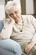 Senior Woman Looking Sad In Chair At Home Stock Photos