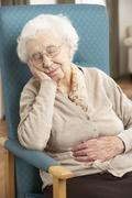 Senior Woman Resting In Chair At Home Stock Photos