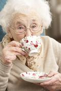 Senior Woman Enjoying Cup Of Tea At Home Stock Photos