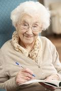 Senior Woman Relaxing In Chair At Home Completing Crossword Stock Photos