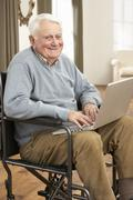 Disabled Senior Man Sitting In Wheelchair Using Laptop - stock photo