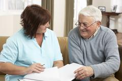 Senior Man In Discussion With Health Visitor At Home Stock Photos