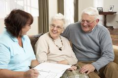 Senior Couple In Discussion With Health Visitor At Home Stock Photos