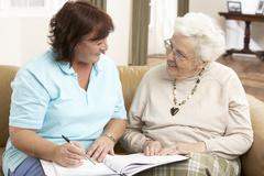Senior Woman In Discussion With Health Visitor At Home Stock Photos