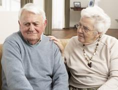 Senior Woman Consoling Husband At Home Stock Photos