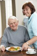 Stock Photo of Senior Man Being Served Meal By Carer