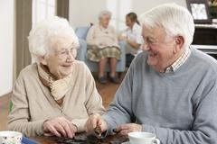 Couple Playing Dominoes At Day Care Centre - stock photo