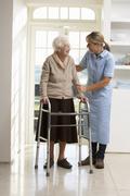 Carer Helping Elderly Senior Woman Using Walking Frame - stock photo