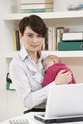 Woman With Newborn Baby Working From Home Using Laptop - stock photo