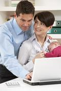 Parents With Newborn Baby Working From Home Using Laptop Stock Photos